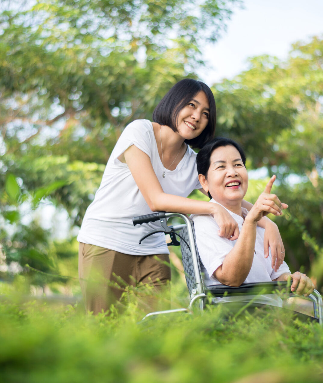 Senior care insurance concept,Caregiver take care to elderly asian woman sitting on wheelchair at outdoor